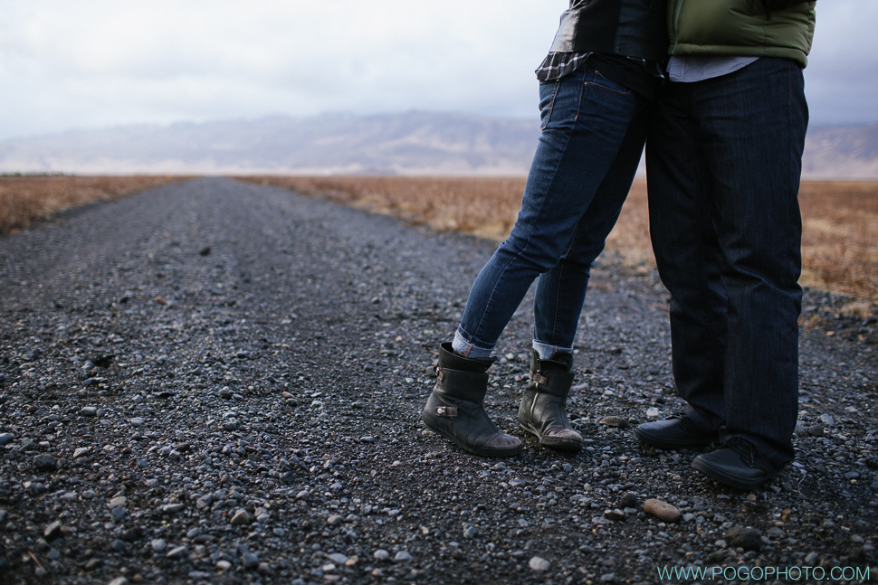 Ankle boots and cuffed denim on black gravel road in Iceland