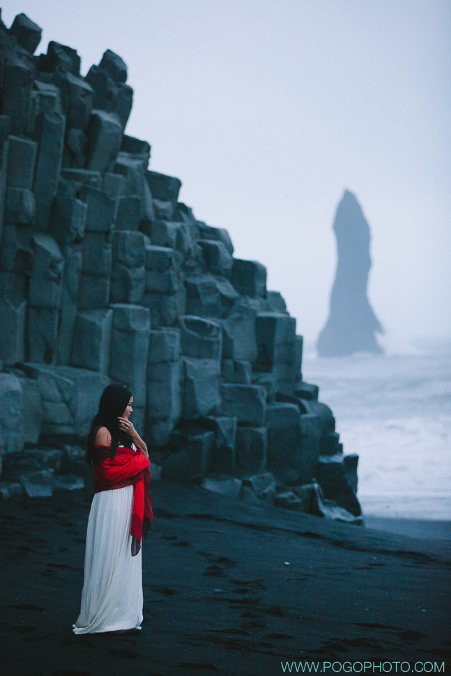 Silk wedding dress with red scarf at Vik black beach in Iceland