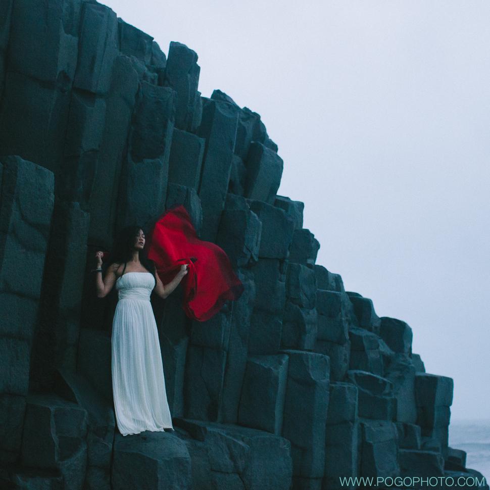 Silk wedding dress with red scarf on basalt columns at Vik black beach in Iceland