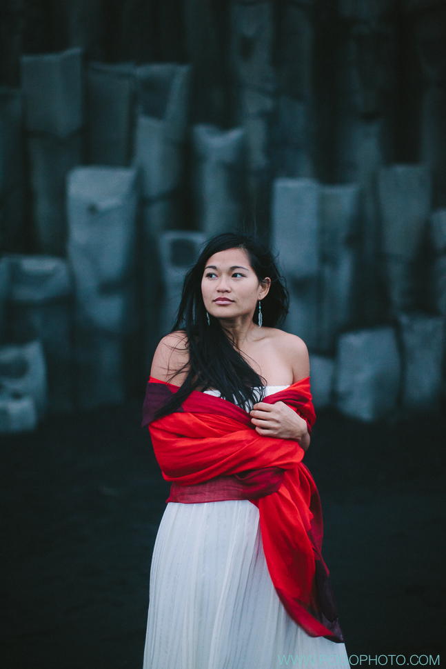 Silk wedding dress with red scarf by basalt columns at Vik black beach in Iceland