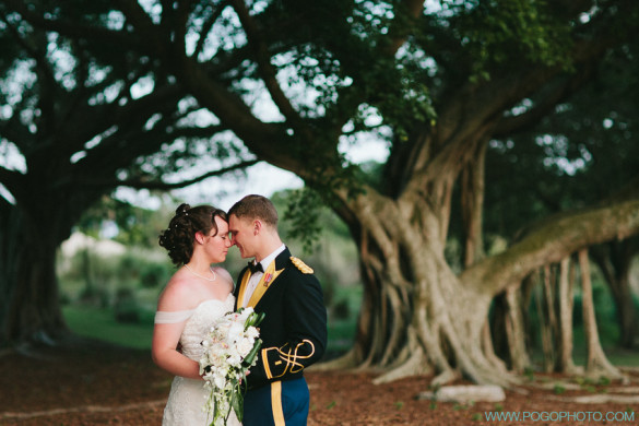 couple shares moment under bany trees during wedding portraits in florida