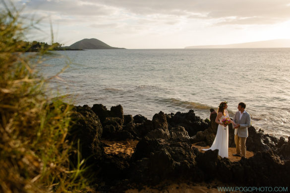 Beautiful and dramatic image of a Maui wedding, bride, groom, and a volcanic cone against the ocean